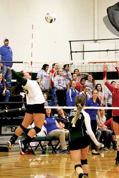 by: JO WHEAT - North Marion senior Kylie Gonzales rises to spike the ball in the Huskies 3-0 loss to Madras Thursday.