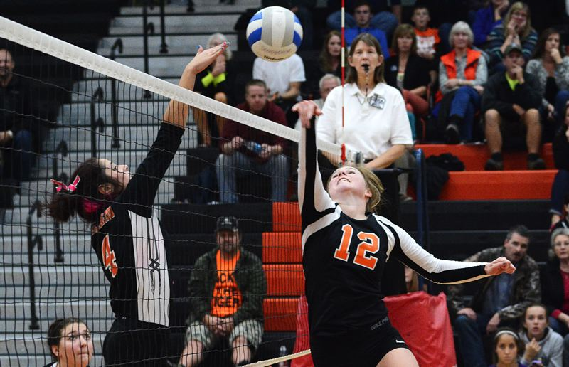 by: JOHN WILLIAM HOWARD - Senior setter Brittany Catlow (12) tips the ball over the net during the Tribe's straight set victory over Yamhill-Carlton on Tuesday evening.