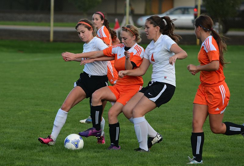 by: JOHN WILLIAM HOWARD - Lauren Frank (11) and senior center back Emily Muth (4) surround Yamhill-Carlton's Carly Christian in the first half of the Tribe's 7-0 victory over the visiting Tigers on Tuesday afternoon.