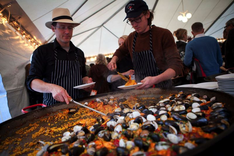 by: TRIBUNE PHOTO: ADAM WICKHAM - Crown Paella owner Scott Ketterman (left) and Ryan Skarl dish up paella at the First to Market event.