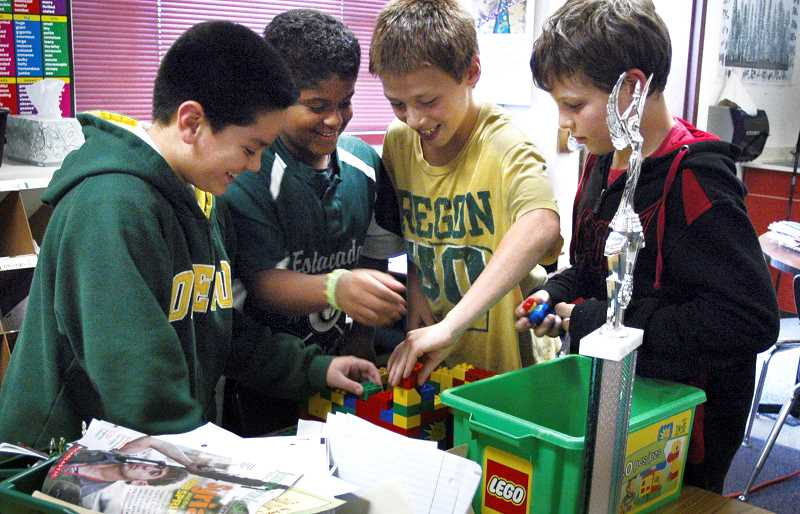 by: ISABEL GAUTSCHI - Jose Vazquez, from left, Charles Narozniak, Justun McAllister and Steven Monahan piece together a Lego fortress.
