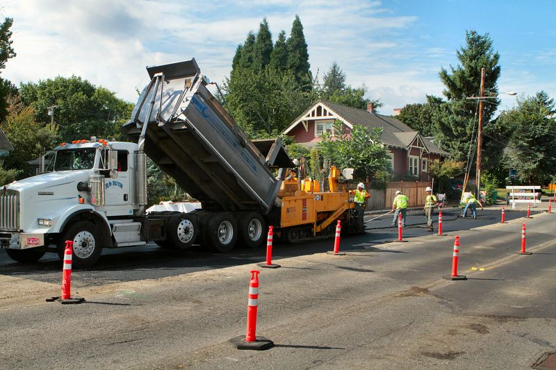 by: DAVID F. ASHTON - Crews lay down a fresh layer of asphalt along S.E. Tacoma Street in Sellwood, over the new Crystal Springs Creek culvert.