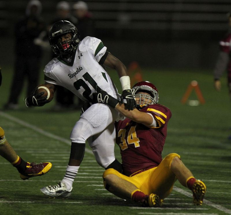 by: TRIBUNE PHOTO: JONATHAN HOUSE - Central Catholics Ryan Nall wraps up Reynolds Hutu Spencer in a high school game last week at Hillsboro Stadium. The Rams won 41-14 and improved their record to 5-0.