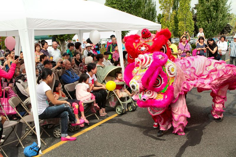 by: DAVID F. ASHTON - Members of the Northwest Dragon & Lion Dance Association excite the Inner Southeast crowd with their antics.