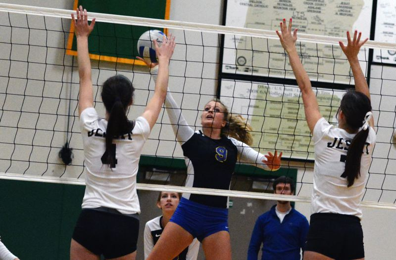 by: TIMES PHOTO: MATT SINGLEDECKER - Aloha senior Jessie Price hits a ball over a Jesuit double-team in the second set of the Warriors loss.
