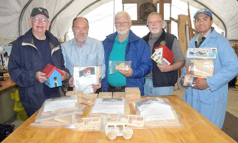 by: GARY ALLEN - Working with wood - The Sawdust Experience group includes (from left to right) Gordon Hont, Kenny Austin, Tom Barnes, Bob Travers and Paulino Rojas. The group spends their free time making wooden toys and wood kits for children.