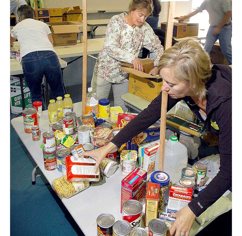 by: GARY ALLEN - Feeding the need - Community members sort food donations at the Newberg Armory last year. The Feed the Need food drive will hold its 10th annual collection on Oct. 13.