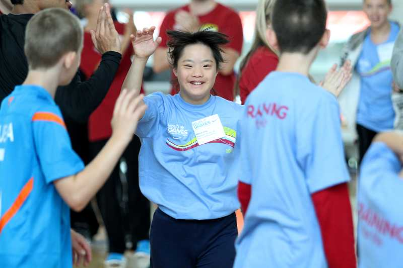 by: TIMES PHOTO: JONATHAN HOUSE - Joanna Wang gives out high-fives during basketball drills on the Nike campus for this year's Special Olympics Oregon.