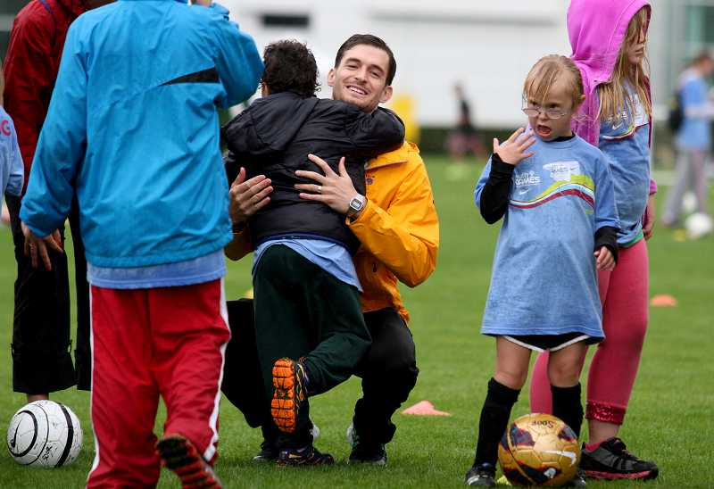 by: TIMES PHOTO: JONATHAN HOUSE - Special Olympics Oregon vounteer Joel Swenson gives a young competitor a hug. Hundreds of children turned out for the event, despite the blustery weather on Saturday.