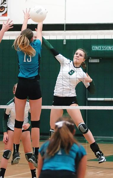 by: DAN BROOD - SMACK -- Tigard sophomore outside hitter Cassie Erickson (9) powers the ball past Century freshman Delaney Seitz during Tueday's match at Tigard. The Tigers triumphed in a three-set sweep.