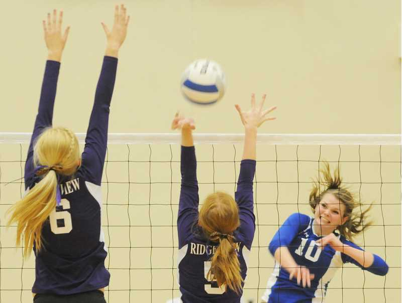 by: LON AUSTIN/CENTRAL OREGONIAN - Karlee Hollis drives the ball past Ridgeviews Chloe Ross and Rhian Sage for one of her 17 kills against the Ravens.