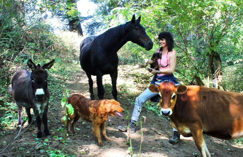 by: OUTLOOK PHOTO: CARI HACHMANN - Surrounded by animals: Stephanie Rickert of Old McDonalds Farm.