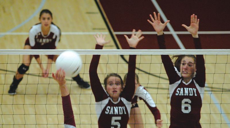 by: SANDY POST: PARKER LEE - Sandys Madison Kansala (5) and Jenny Covington (6) go up for a block during last weeks four-set loss to Sherwood.