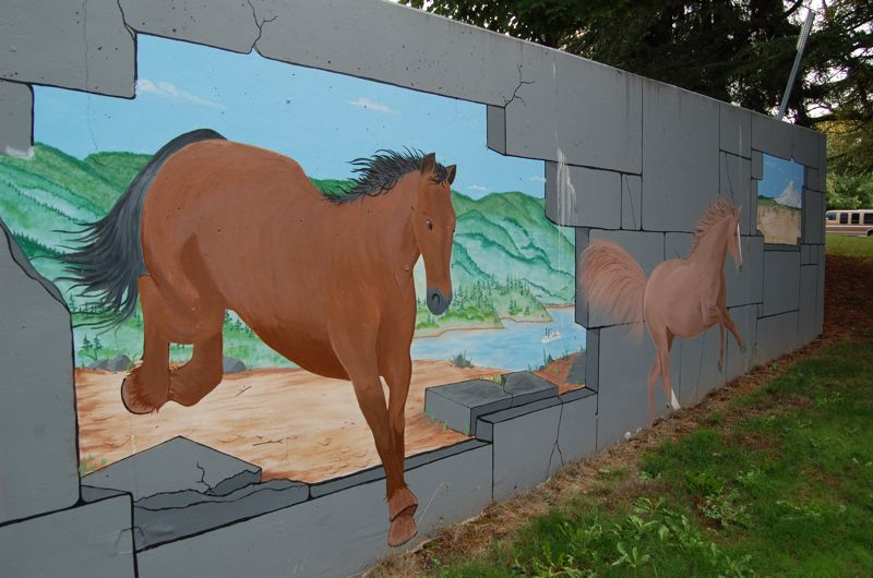 by: PHOTO BY: RAYMOND RENDLEMAN - This trompe l'oeil design suggests mustangs are coming through a wall in front of Milwaukie High School. Milwaukie could see more murals if City Council passes code changes.