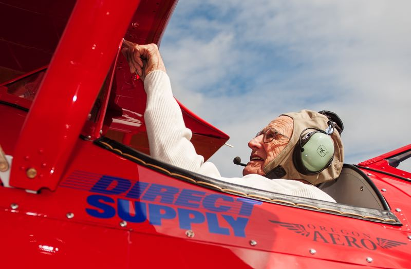 by: SPOKESMAN PHOTO: JOSH KULLA - Duane 'Buck' Buckmaster goes over the controls and cockpit of the Stearman Kaydet biplane he flew in recently, courtesy of Ageless Aviation, a national non-profit group that works to connect veterans with their past.