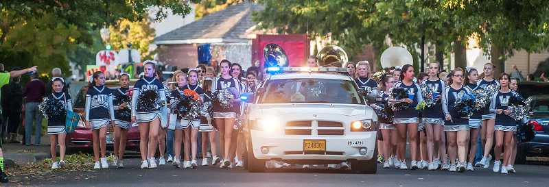 by: SPOKESMAN PHOTO: JOSH KULLA - Wilsonville High School cheerleaders lead the parade from the school down Wilsonville Road on Oct. 4.