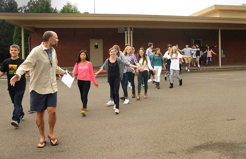 by: VERN UYETAKE - Students file out of the building with their arms extended, a practice showing that they are unarmed, during a recent fire drill at Lake Oswego Junior High School.