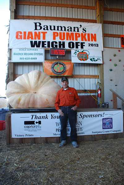 by: SUBMITTED - Clyde Wilson of Chehalis, Wash., poses with his giant pumpkin, which won first place in the Great Pumpkin Weigh Off at Bauman Farms on Saturday.