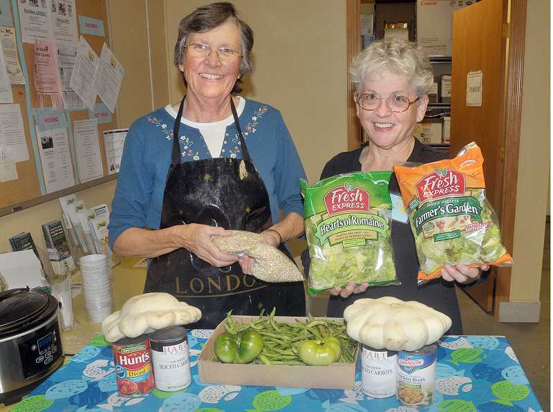 by: GARY ALLEN - Teachers - Judith Labadie (left) and Marilyn Godfrey volunteer with Newberg Friends In Service to Humanity providing food boxes to needy citizens. Three months ago they started offering food tastings, showing clients how to prepare unusual meals from unusual ingredients.