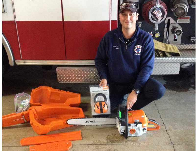 by: MOLALLA FIRE DISTRICT - Lt. Clint Shaver of the Molalla Fire District with the new Stihl saw donated by Ronda Rozzel.