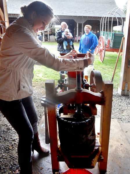 by: CONTRIBUTED - Kelcie Collins presses her luck with an authentic cider press.