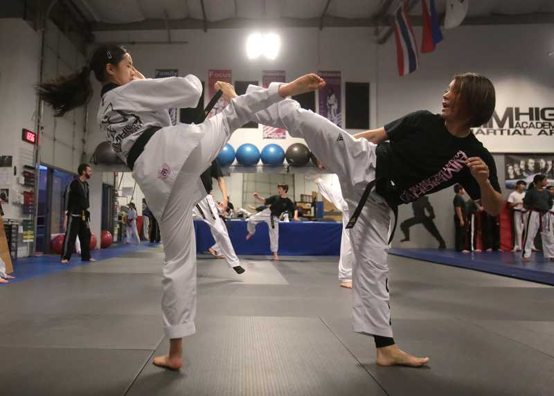 by: TIMES PHOTO: JONATHAN HOUSE - Nina Chen, left, and Donna Bowton spar during practice at the Aim High Academy of Martial Arts.