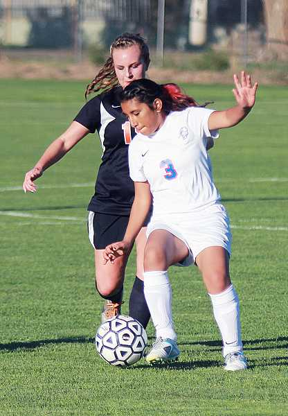 by: BILLY GATES/THE PIONEER - Madras' Gema Zamora tries to work the ball past a Molalla defender.