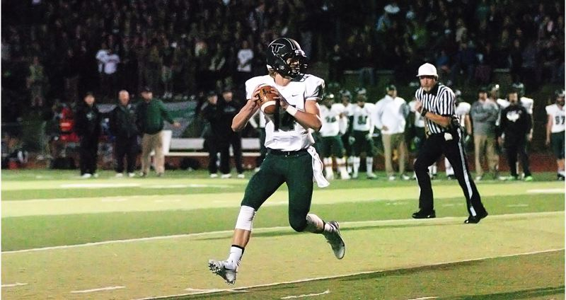 by: DAN BROOD - ROLLING OUT -- Tigard senior quarterback Jett Even looks for a receiver during Friday's game at Tualatin.
