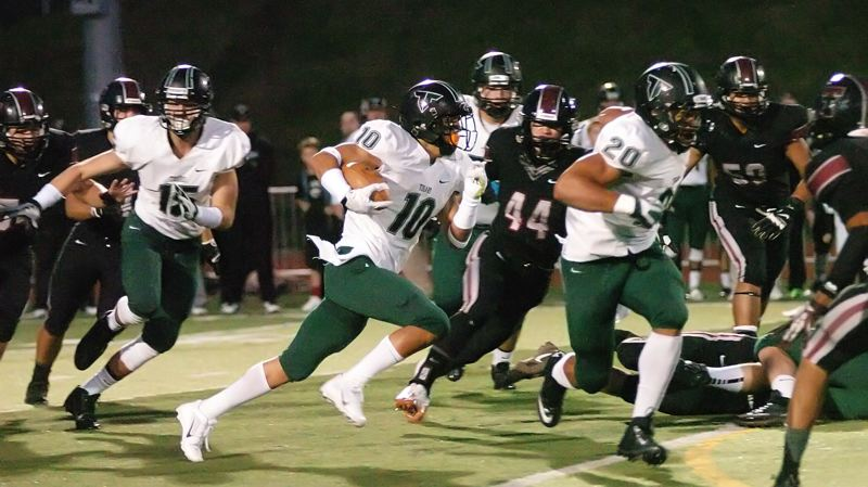 by: DAN BROOD - FULL SPEED -- Tigard senior Manu Rasmussen (10), running  behind the block of senior A.J. Hotchkins, is on his way to scoring on a 63-yard run.