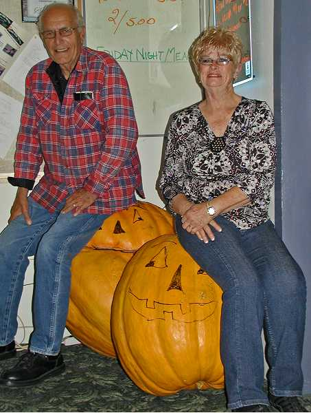 by: RON HALVORSON - Jack Berman (LEFT) and Charlee Harmon (RIGHT) sit on top of the two giant pumpkins being used for the Alzheimer's Research fundraiser at the Prineville Eagles Lodge.