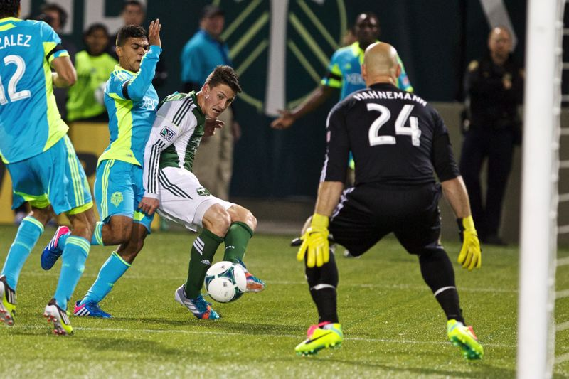 by: TRIBUNE PHOTO: JAIME VALDEZ - Portland Timbers midfielder Ben Zemanski takes a shot against Seattle Sounders FC goalkeeper Marcus Hahnemann (right) in the second half Sunday night at Jeld-Wen Field.
