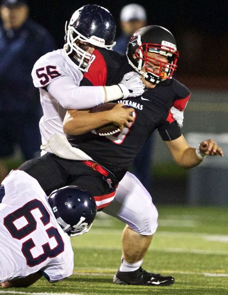 by: JAIME VALDEZ - Clackamas quarterback Doonie Johnson is unable to escape Lake Oswego defenders Collln Calhoon (55) and Austin Wright (63), as Johnson is sacked during last weeks game with the Lakers. The Cavaliers could do little right, and Lake Oswego prevailed 42-18, ending a Cavalier win string at six games.