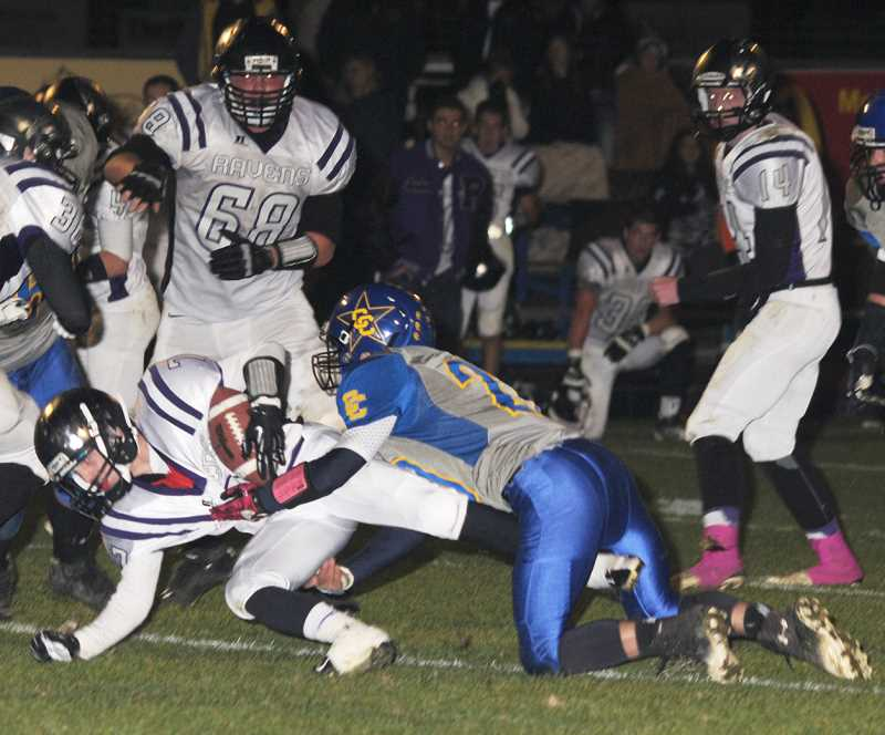 by: LON AUSTIN/CENTRAL OREGONIAN - Cole Ovens tackles Tanner Stevens for a short gain. Ovens finished with six tackles for the Cowboys in a defensive battle against the Ridgeview Ravens.