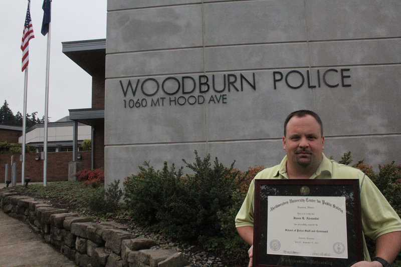 by: JEFF MCDONALD  - Capt. Jason Alexander of the Woodburn Police Department shows off his diploma from Northwestern University for Public Safety in Nashville, Tenn., where he recently completed 10 weeks of administrative training.