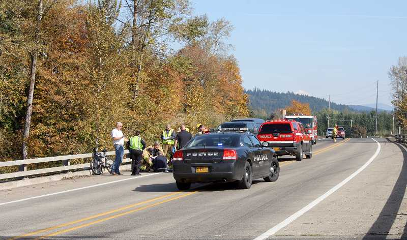by: PEGGY SAVAGE - Molalla paramedics and police care for an injured person on a bridge over the Molalla River on Highway 211 near Meadowbrook