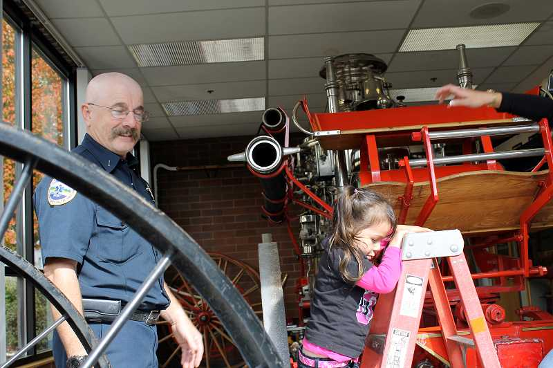 by: NEWS-TIMES PHOTO: JOHN SCHRAG - Stephen Prichard, a Forest Grove Fire & Rescue volunteer firefighter at the Gales Creek station, visited the Forest Grove site Saturday to help with the public safety open house. He manned the room where FGF&R keeps its 1906 pumper and helped children climb up and down from the antique emergency vehicles seat.