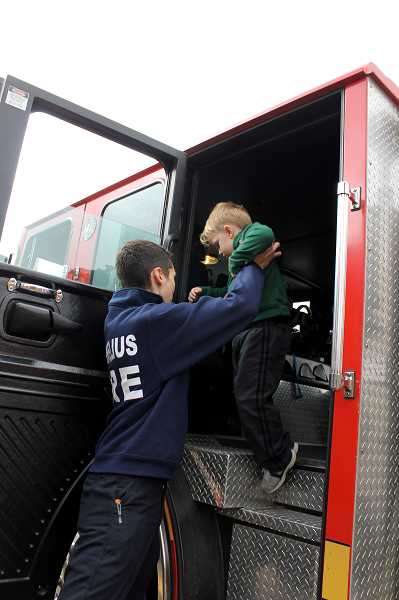 by: NEWS-TIMES PHOTO: JOHN SCHRAG - FGF&R volunteer Max Randall gives a boost to 4-year-old Kyler Holton of Cornelius Saturday. The department had two rigs running to give youngsters rides around the block.