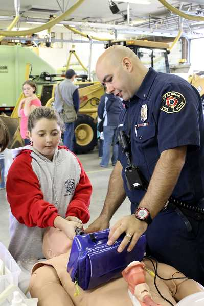by: NEWS-TIMES PHOTO: JOHN SCHRAG - Lt. Will Murphy, FGF&Rs EMS officer, offers guidance to 9-year-old Carmyn Russell, as she inserts a tube into a dummy used for emergency medical training.  Russel, a third grader at Harvey Clarke Elementary School, has a strong interest in medicine, according to her mom, Jamie Russell, who said her daughter used her allowance money to buy a Forest Grove Fire & Rescue sweatshirt on Saturday.