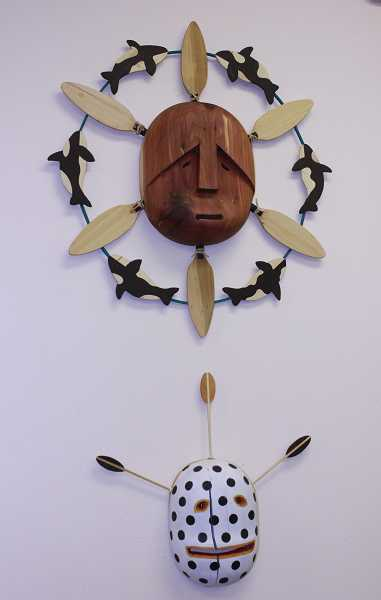 Two of the many handcarved masks hung on the walls of the library through the second week of November.