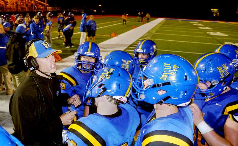 by: SETH GORDON - Pep talk - Newberg head coach T.J. Tomlin instructs his players during a break in the action Friday night. After falling behind 14-0, the Tigers stormed to a 31-21 victory.