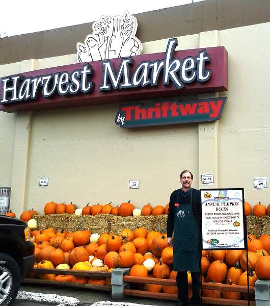 by: ISABEL GAUTSCHI - Store Director Mike Schuh stands before 4 tons of pumpkins at the Estacada Harvest Market. All of the October sale profits from these pumpkins will be donated to the Estacada School District.