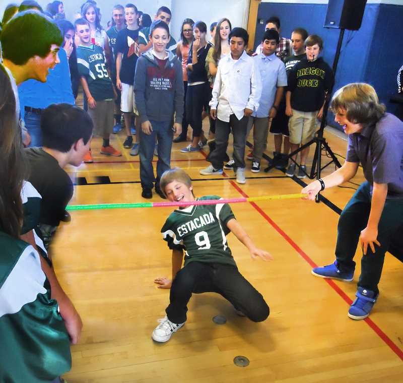 by: DANTE TORGERSEN - Jason Schaffer does the limbo during the Estacada Junior High School's Incentive Day on Friday, Oct. 4. Logan Tallmon (holding the pole) finds it amusing.