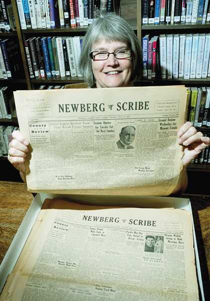 by: GARY ALLEN - Old news - Denise Reilly, reference librarian at the Newberg Public Library, holds a copy of the Newberg Scribe, which began publishing in 1931 under the direction of Editor John D. Burt, formerly of the Carleton Sentinel. He was later joined by Associated Editor Don Woodman, formerly    of the Yamhill Spokesman. When the Scribe was first introduced, it was actually called the Newberg Scribe and Carleton Sentinel.