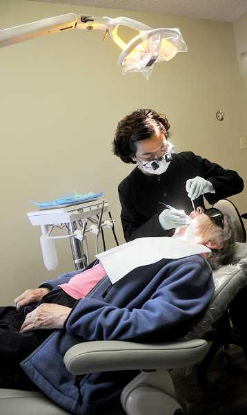by: GARY ALLEN - New in town - Newberg ­dentist Angela Toy checks a patient's teeth in her new practice, Arbor Hills Dental. Toy opened shop in late September at 504 Villa Road Suite 1.