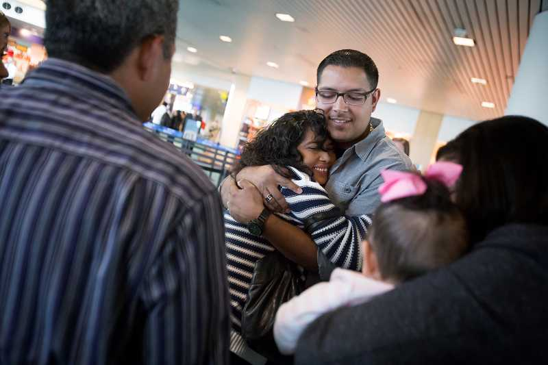 by: TIMES PHOTO: JONATHAN HOUSE - Irma Diaz hugs her son Luis Jr. at Portland International Airport after spending seven years in Guatemala, while waiting to return home to the United States.