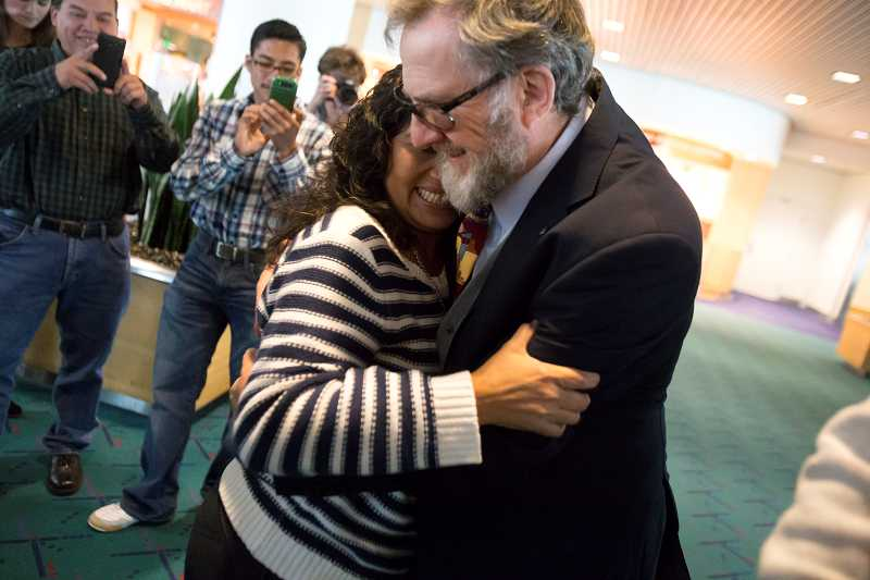 by: TIMES PHOTO: JONATHAN HOUSE - The Diaz family's immigration attorney, Tilman Hasche, hugs Irma after her arrival at Portland International Airport from Guatemala. Hasche's pro-bono work for the family was instrumental in their reunion.