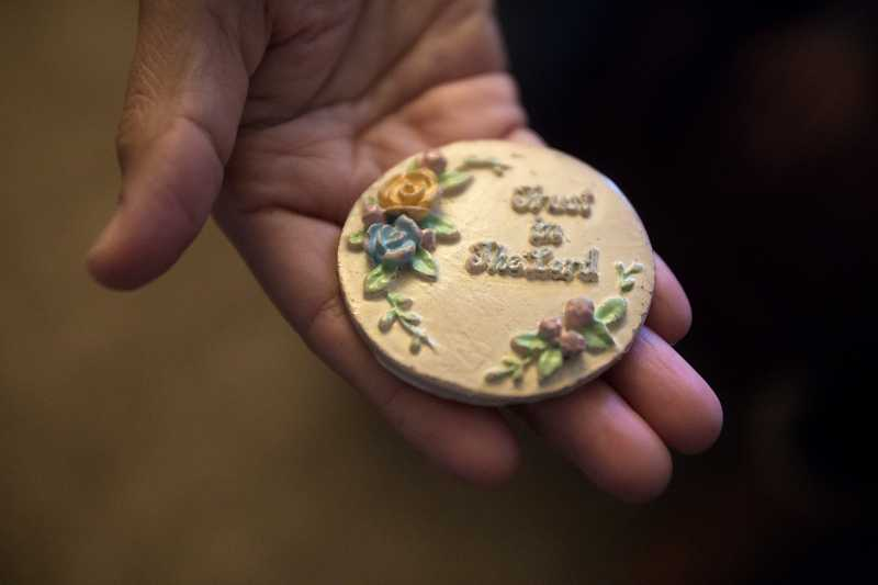 by: TIMES PHOTO: JONATHAN HOUSE - Irma Diaz holds a pendant stating 'Trust in The Lord' that she picked up after it fell off a cross. She held unto it every day for the past seven years, trusting that one day her family would be reunited.