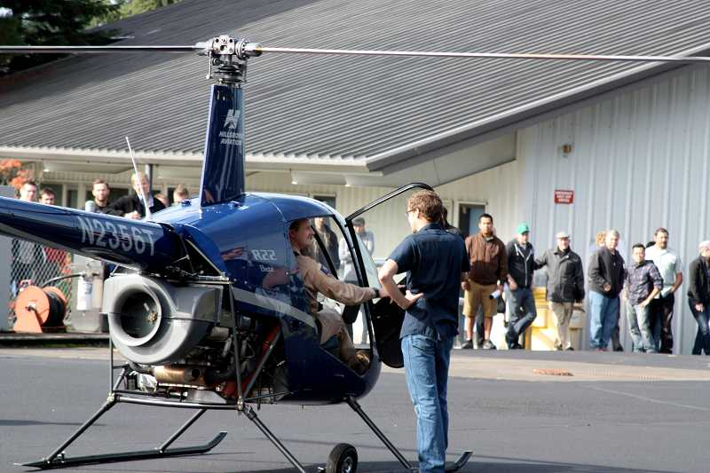 by: SUBMITTED PHOTO: PCC - Seth Hansen (right), Hillsboro Aviations director of maintenance, welcomes the R-22s pilot to the Rock Creek Campus for the Aviation Maintenance Technologys Career Day as students look on in the background.