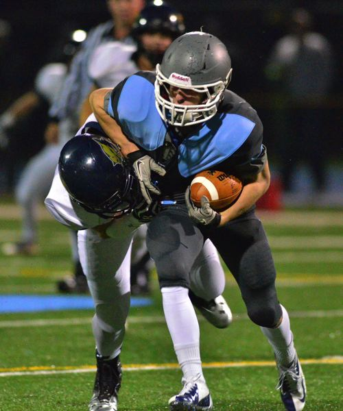 by: VERN UYETAKE - Lakeridge's Holden Catlett tries to shake a tackle in the Pacers' 28-14 win over Canby last week.