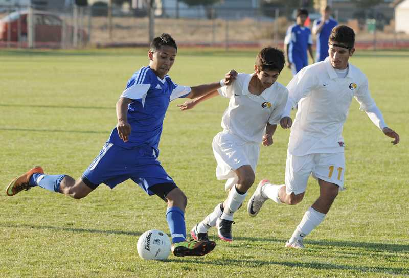 by: LON AUSTIN/CENTRAL OREGONIAN - Victor Villagomez drives past a pair of Redmond Panther defenders during the Cowboys 2-0 win over the Panthers Tuesday afternoon. The Cowboys broke open a 0-0 tie with two second half goals to seal the win. Crook County is now 6-4-1 on the year.